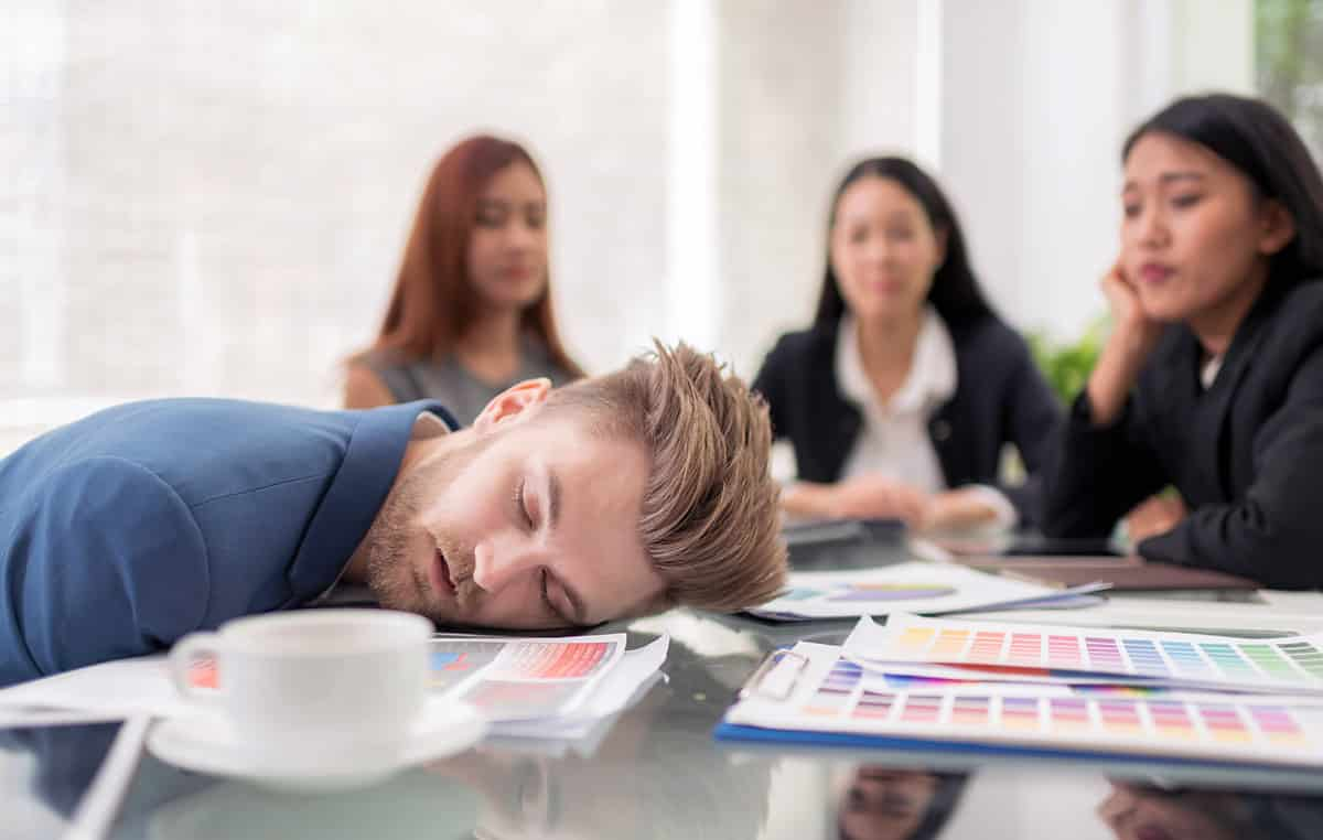 man sleeping on desk during a meeting