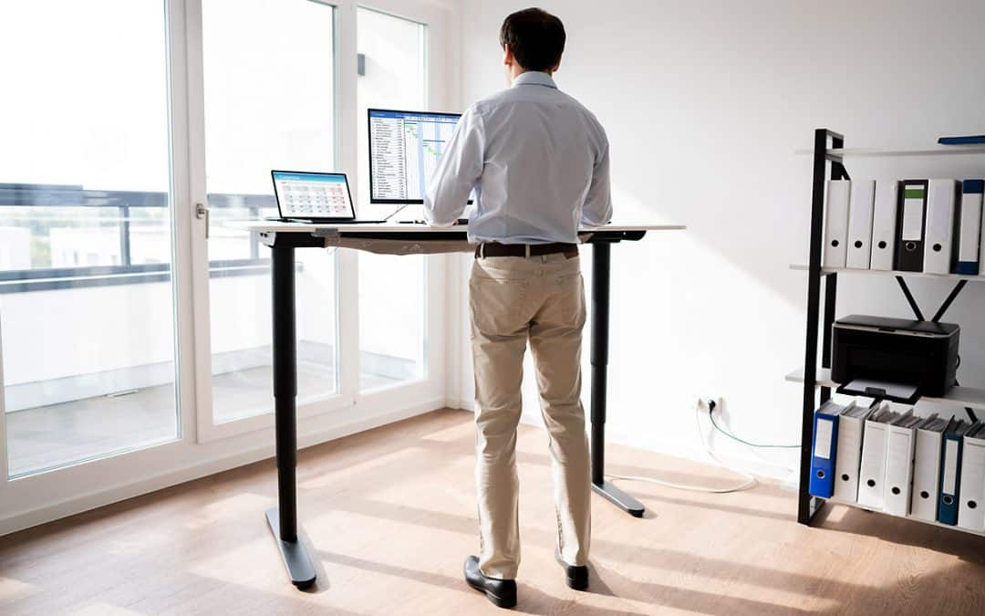 man working on computer at a standing desk