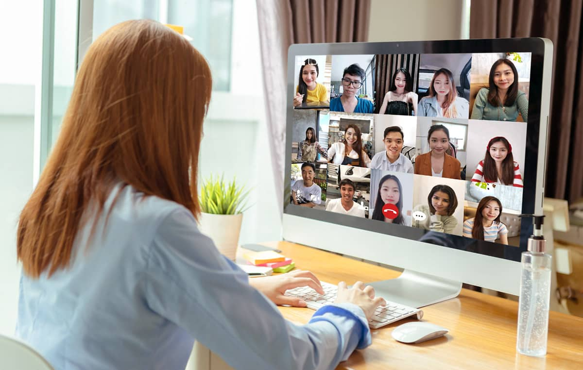 woman having a video call with multiple people on computer screen