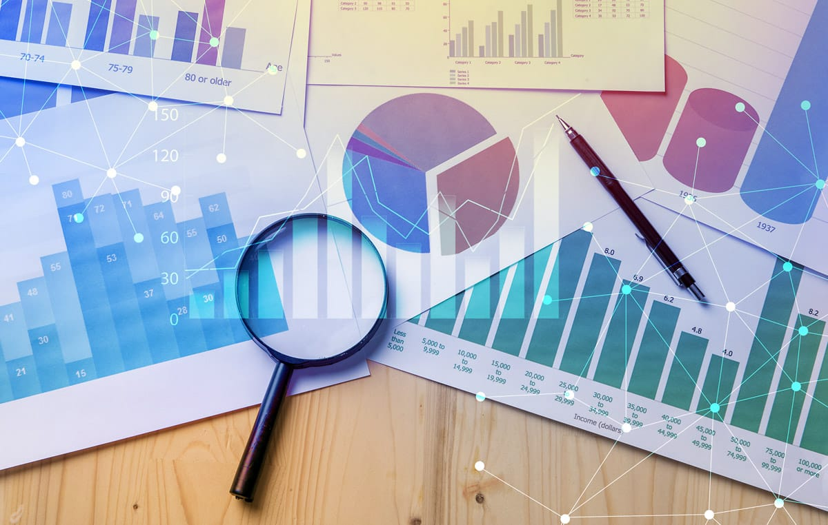 magnifying glass on top of stats and graphs