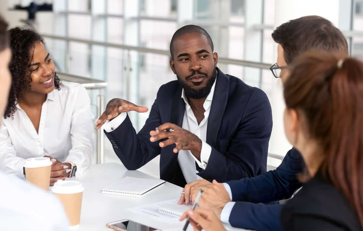 man talking with colleagues around a table at work
